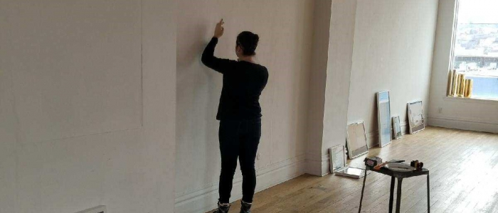 Catherine Gannon installs part of the art exhibit she helped create for her FE-R project
